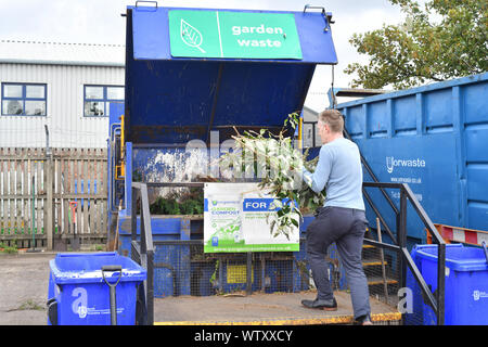 man carrying garden cuttings for recycling into compost at household recycling centre united kingdom - Stock Photo