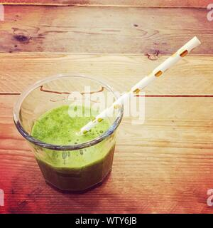 Close-up Of Green Smoothie Served In Glass On Table - Stock Photo