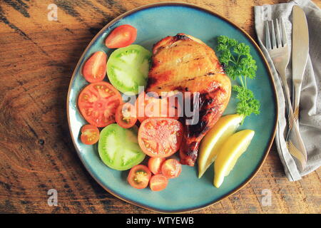 Grilled chicken leg quarters with crispy golden brown skin, tomatoe ,lemon on dark wooden boards. Food background. Top view - Stock Photo