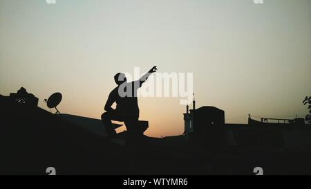 Rear View Of Man Pointing Towards Sky While Standing On Rooftop During Sunset - Stock Photo