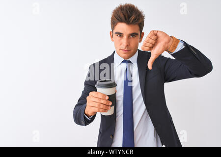 Young handsome businessman wearing suit holding coffee over isolated white background with angry face, negative sign showing dislike with thumbs down, - Stock Photo