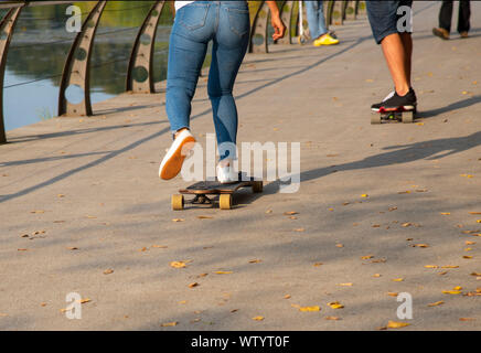 People go along the waterfront on a skateboard, photographed from the waist down. - Stock Photo