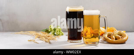 Various types of freshly poured beer - light and dark and snack variety. Beer ingredients in the background. Banner. Copy space. - Stock Photo