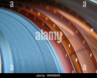 Roll of developed Super 16mm Film Negative on a Bobby in a can. 16mm Film is a popular and economical gauge of film stock. - Stock Photo