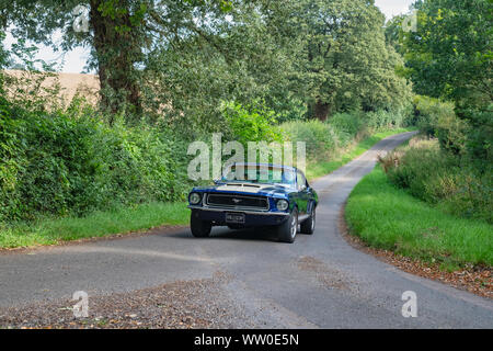 1968 Ford Mustang going to a classic car show in the Oxfordshire countryside. Broughton, Banbury, England - Stock Photo