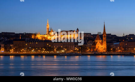 BUDAPEST, HUNGARY - APRIL 15, 2013: Szilágyi Dezső Square Reformed Church and Matthias Church on the west bank of the river Danube at the blue hour. - Stock Photo