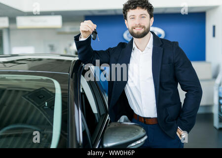 Happy buyer holding keys near the car in front of the modern avtosalon building - Stock Photo