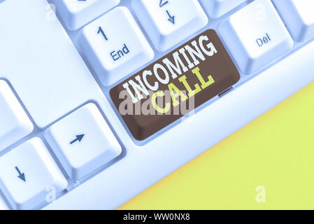 Word writing text Incoming Call. Business photo showcasing Inbound Received Caller ID Telephone Voicemail Vidcall White pc keyboard with empty note pa - Stock Photo