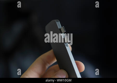 Man's hand holding The USB adapter under the Type-C connector for laptop. Multiport station for laptop with multiple different ports. USB to USB Type - Stock Photo