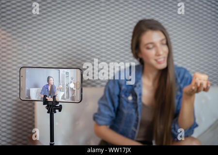 Young beauty blogger selling her cosmetic on live stream broadcasting by mobile phone. - Stock Photo