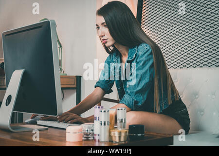 Casual woman working on her iMac pro at home. - Stock Photo
