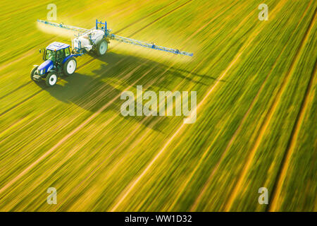 Aerial view of farming tractor  spraying on field - Stock Photo