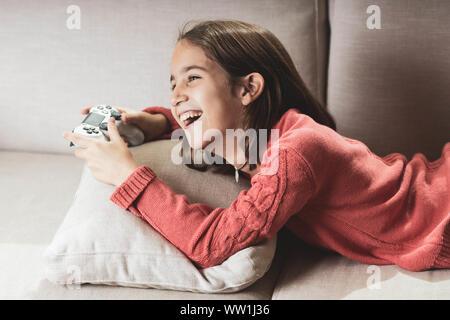 Niña jugando en casa con la videoconsola tumbada en el sofá - Stock Photo