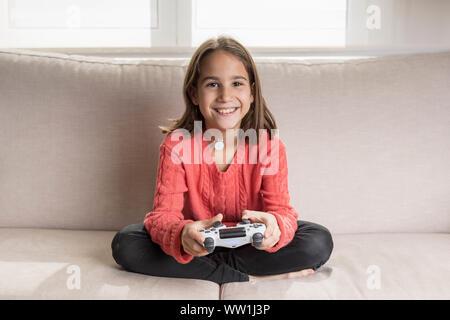 Niña jugando en casa con la videoconsola sentada en el sofá - Stock Photo