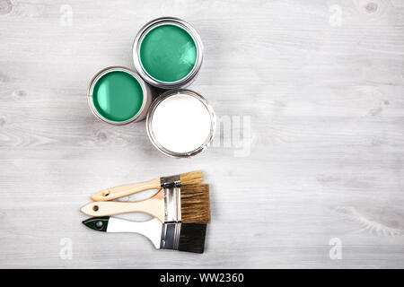 Green paint cans and colored brushes on white wooden background