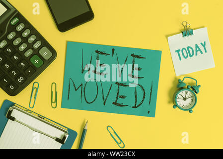 Writing note showing We Ve Moved. Business concept for To go from one residence or location to another Relocate Clipboard sheet calculator pencil cloc - Stock Photo