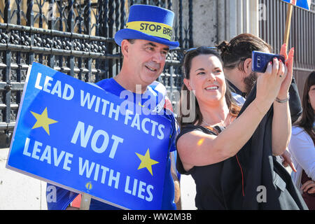 Westminster, London, UK. 12th Sep, 2019. A passer-by takes a selfie with 'Stop Brexit Man' Steven Bray, also known as Westminster's 'Stop Brexit Man'. Anti-Brexit protesters from SODEM (Stand of Defiance European Movement) rally with placards and flags outside the main gates at Parliament today. Credit: Imageplotter/Alamy Live News - Stock Photo
