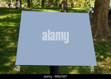 Blank blue sign on pedestal with a green grass and trees park like background - Stock Photo