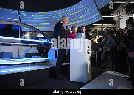 Frankfurt, Germany. 12th Sep, 2019. German Chancellor Angela Merkel (C) takes a tour of the exhibiton after the opening ceremony of the International Motor Show (IAA) 2019 in Frankfurt, Germany, Sept. 12, 2019. Germany's International Motor Show (IAA) 2019 opened officially on Thursday in Frankfurt, with a discussion of the future of mobility from industry representatives and government leaders. Credit: Lu Yang/Xinhua/Alamy Live News - Stock Photo