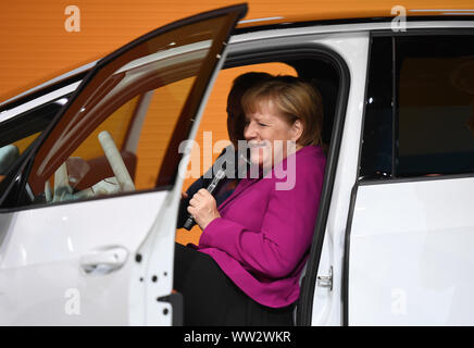 Frankfurt, Germany. 12th Sep, 2019. German Chancellor Angela Merkel tries a Volkswagen ID. 3 electric car at the International Motor Show (IAA) 2019 in Frankfurt, Germany, Sept. 12, 2019. Germany's International Motor Show (IAA) 2019 opened officially on Thursday in Frankfurt, with a discussion of the future of mobility from industry representatives and government leaders. Credit: Lu Yang/Xinhua/Alamy Live News - Stock Photo