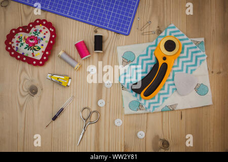 Flat lay image of sewing tools, equipment and accessories on wooden table top
