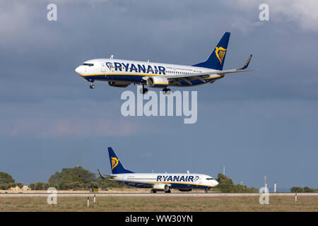 Ryanair Boeing 737-8AS (REG: EI-DWI) coming in to land while another Ryanair 737 (EI-DHG) waits on Alpha loop for take off. - Stock Photo
