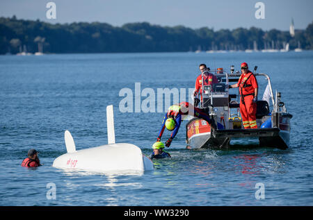 12 September 2019, Bavaria, Prien: Rescuers of the German Life and Rescue Society (DLRG) demonstrate on Lake Chiemsee the rescue of a dinghy that has fallen over its head in distress. On the occasion of the Day of Water Rescue, the Deutsche Lebens-Rettungs-Gesellschaft (DLRG) presented various exercise scenarios on Lake Chiemsee. Photo: Matthias Balk/dpa - Stock Photo
