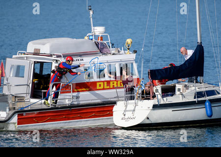 12 September 2019, Bavaria, Prien: Rescuers of the German Life and Rescue Society (DLRG) demonstrate an operation scenario on Lake Chiemsee in which a man on a sailboat has to receive medical care. On the occasion of the Day of Water Rescue, the Deutsche Lebens-Rettungs-Gesellschaft (DLRG) presented various exercise scenarios on Lake Chiemsee. Photo: Matthias Balk/dpa - Stock Photo