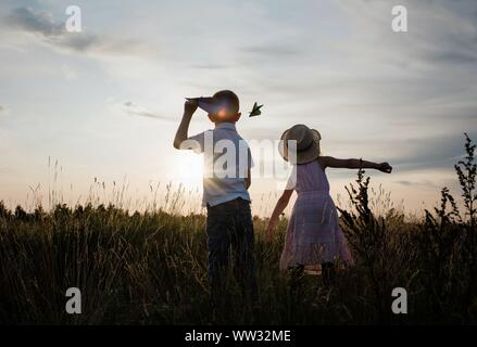brother and sister flying planes playing in a meadow at sunset
