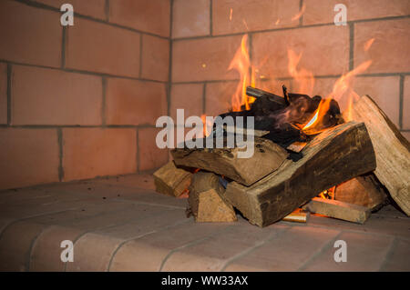 Logs burning together with coal on a grill. - Stock Photo