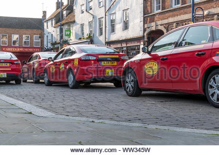 Steve's Mini Cab / taxi hire vehicles in a row at St Neots in Cambridgeshire, England, UK - Stock Photo
