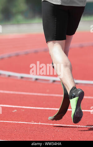athlete with prosthesis on the leg in the running track of sport venue - Stock Photo