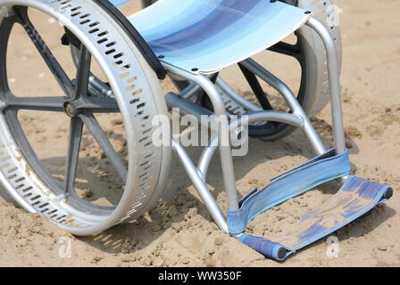 big wheel in aluminium of wheelchair on the beach - Stock Photo
