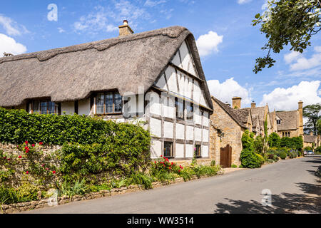 Old half timbered buildings and stone houses beside the lane in the Cotswold village of Stanton, Gloucestershire UK