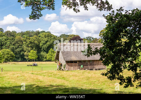 The wooden, thatched cricket pavilion raised up on staddle stones in the Cotswold village of Stanway, Gloucestershire UK - It was built in 1925 by Joh - Stock Photo