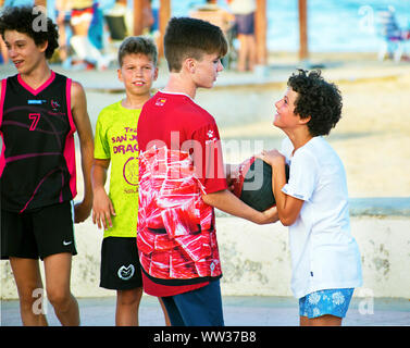 Murcia, Spain, August 24, 2019: Group of friends playing basketball in the street close to the beach. - Stock Photo