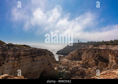 Cliffs, hills and rocky landscape and valleys of the Algarve's Coast with, in the distance, the Alfanzina Lighthouse, Portugal - Stock Photo