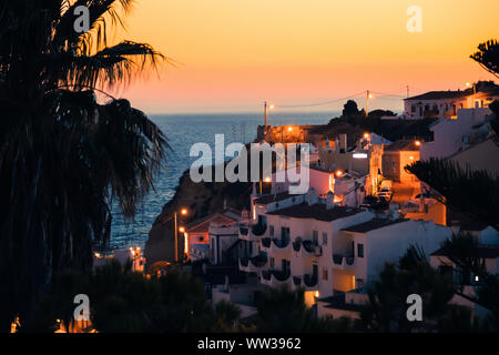 Beautiful view of a palm tree, Mediterranean houses and a sunset at Carvoeiro Beach in Algarve, Portugal - Stock Photo
