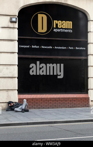 Ironic image of a young man sleeping on the street in front of a rental sign for dream apartments in Liverpool - Stock Photo