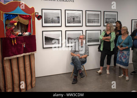 Martin Parr photographer ( sitting ) at the Martin Parr Foundation MPF  gallery Bristol. Exhibition work by Marketa Luskacova 2010s 2019 HOMER SYKES Stock Photo