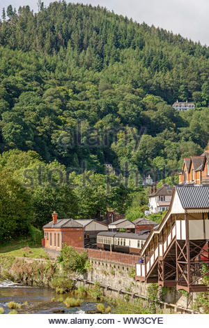 Llangollen railway station underneath a tree covered hill.   Railway carriages are beside a platform with a footbridge in the foreground. - Stock Photo