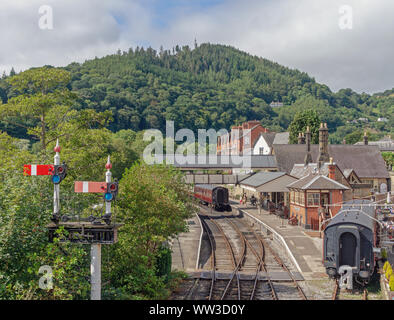 Llangollen railway station underneath a tree covered hill.  Railway carriages are in a siding and there is a signal in the foreground. - Stock Photo