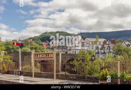 Llangollen railway station platform with location sign and signal.  A bridge and white buildings are in the background with hills forming a backdrop. - Stock Photo