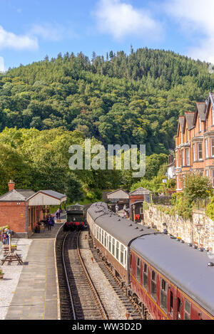 Llangollen railway station underneath a tree covered hill.   Railway carriages are beside a platform with a train engine on an adjacent track. - Stock Photo
