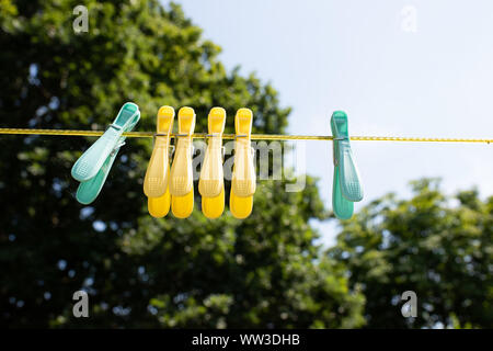 coloured pegs hanging on a washing line in an english country garden - Stock Photo