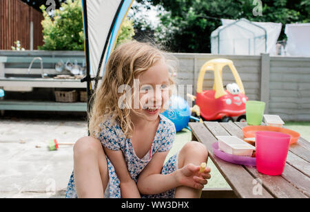 young blonde girl smiling eating lunch at home outside in england - Stock Photo