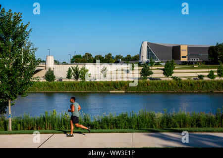 A man jogs along path in a city park against river and tall buildings
