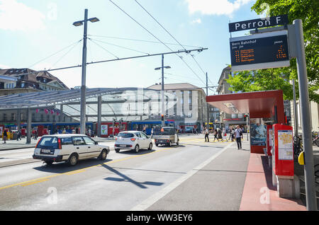 Bern, Switzerland - August 14, 2019: Bus station by the main train station in the center of the Swiss capital. Public transport. People on the street. Cars on the road. Intersection. Daily life. - Stock Photo