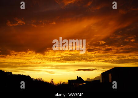 burning sky over the city, clouds like fire at sundown - Stock Photo