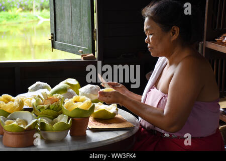 Kanchanaburi, Thailand, 09.09.2019: A local Thai woman in traditional Thai, Siamese dress is pealing pomelos and preparing delicious artworks from the - Stock Photo
